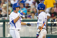 Florida Gators designated hitter JJ Schwarz (22) is greeted by teammate Dalton Guthrie (5) after scoring against the Miami Hurricanes in the NCAA College World Series on June 13, 2015 at TD Ameritrade Park in Omaha, Nebraska. Florida defeated Miami 15-3. (Andrew Woolley/Four Seam Images)