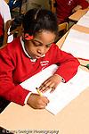 Parochial School Bronx New York  Kindergarten girl writing in notebook sitting at desk vertical