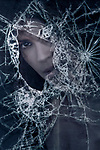 Closeup of a young caucasian woman face looking from behind a broken window glass, conceptual dramatic portrait.