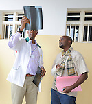 Major William Kanyankore, Medical Director of Gisenyi District Hospital, consults with a patient who is recovering from a machete slash on his arm by an assailant..Northwest Rwanda....
