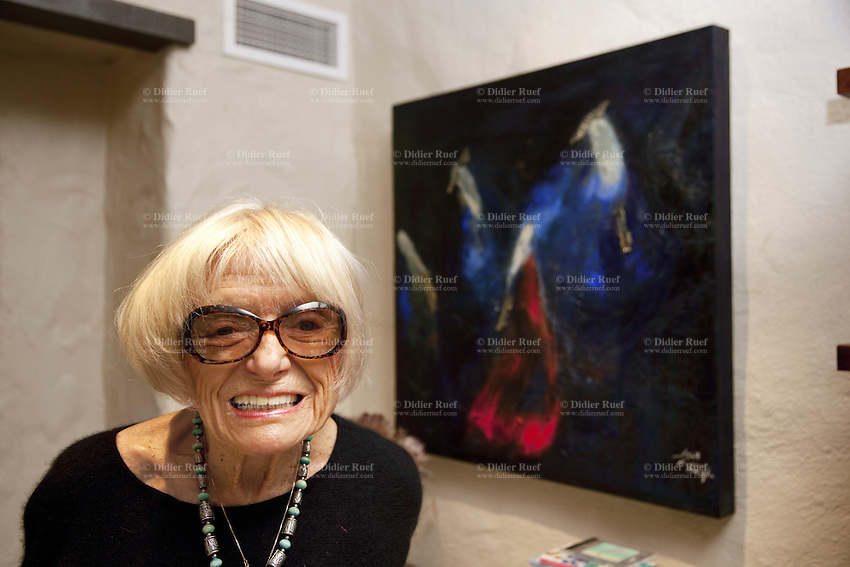 USA. California state. Napa valley. Margrit Biever Mondavi in her office at Robert Mondavi Winery, To Kalon Vineyard. She stands up close to one her paintings. Margrit Biever Mondavi (born 1926 in Switzerland) is Vice President of Art and Culture at Robert Mondavi Winery which she joined in 1967. Under her direction, Robert Mondavi Winery developed original cultural and culinary arts programs. In 1980, she married Robert Mondavi and worked with him in many of his philanthropic activities. The flag of Switzerland consists of a red flag with a white cross (a bold, equilateral cross) in the centre. It is one of only two square sovereign-state flags. 16.12.2014 © 2014 Didier Ruef