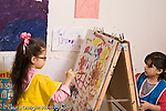 Education preschool 4 year olds art activity two girls wearing smocks painting at easel horizontal