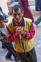 Bodhnath, Nepal.  Worshiper Praying at Buddhist Shrine.