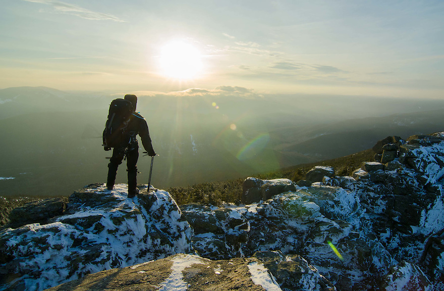 A lone winter hiker takes in the view from the Franconia Ridge Trail, high atop the mountains which form New Hampshires Franconia Notch.