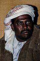 Oman.  Omani Afro-Arab Musician Wearing Traditional Omani Msarr (Headwear).