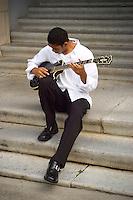 Guitar player on university steps.