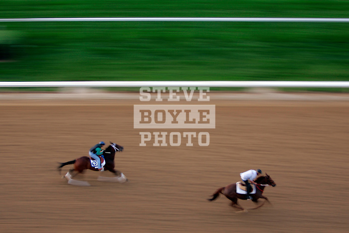 Two horses and jockeys practice on the track at Churchill Downs during a morning workout in Louisville, Kentucky on May 6, 2006.  Barbaro, ridden by Edgar Prado, won the 132nd Kentucky Derby in the tenth race of the day......