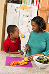 Mother and son, age 5, in kitchen, mother preparing salad and talking to son