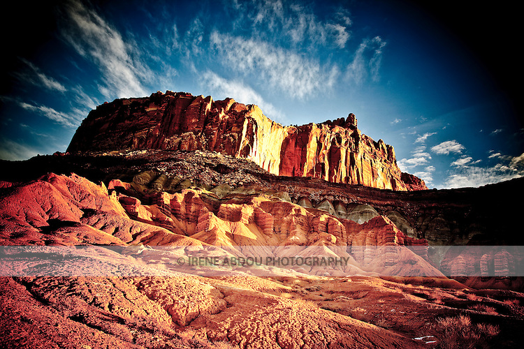 The rock formations of Capitol Reef National Park in southern Utah glow orange in the early sunrise light.