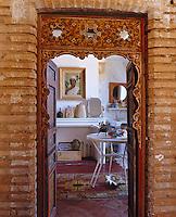 A view into a bathroom through a Moorish door fitted into a brick doorway