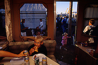 Supplied with a table, seats, pizza, and root beer, a camper makes a convenient place to refuel before exploring the evening action at Minnesota's Nobles County Fair in Worthington MN.