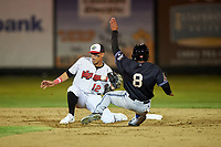Great Falls Voyagers shortstop Lency Delgado (12) prepares to apply the tag to Cesar Garcia (8) during a Pioneer League game against the Missoula Osprey at Centene Stadium at Legion Park on August 19, 2019 in Great Falls, Montana. Missoula defeated Great Falls 1-0 in the second game of a doubleheader. (Zachary Lucy/Four Seam Images)