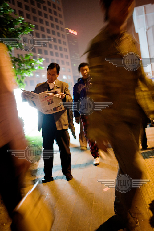 A city worker reads the newspaper during rush hour in the Central Business District.