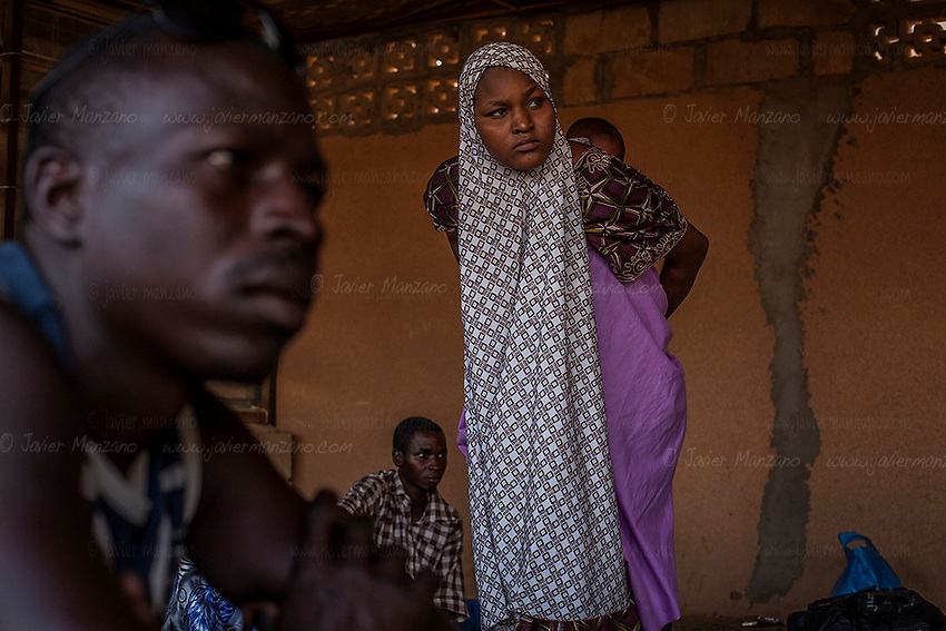 """AGADEZ, NIGER — <br /> Migrants, housed in what is commonly referred to as a """"ghetto"""", wait for night fall before packing their belongings on the small pick-up trucks that will drive them through the desert on their way to Libya."""