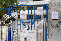 """Pictured: A funeral announcement is posted next to flowers and tributes left at the gate of the 6th primary School in Acharnes, Athens, Greece. Saturday 10 June 2017<br /> Re: An 11 year old boy has been shot dead by a """"stray bullet"""" during a school celebration in Acharnes (Menidi) area, in the outskirts of Athens, Greece.<br /> Marios Dimitrios Souloukos """"complained to his mum"""" who works as a teacher at the 6th Primary School of Acharnes that he was feeling unwell, he then collapsed with blood pouring out from the top of his head.<br /> His mum tried to revive him assisted by other teachers while his schoolmates who were reportedly upset, were hurriedly removed by their parents.<br /> According to locals an ambulance arrived 25 minutes late.<br /> Hundreds of police officers have been deployed in the area and have raided many properties.<br /> Shells matching the fatal bullet which hit the boy on the top of his head were found in a house yard nearby.<br /> Local people reported hearing shots being fired at a nearby Romany Gypsy camp before the fatal incident.<br /> The area has been plagued with criminality during the last few years."""