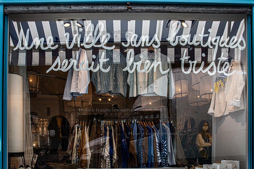 """negozio di abbigliamento con scritta """" una città senza negozi sarebbe molto triste"""""""