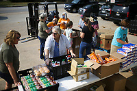 Volunteer Vicki Cowling (from left) and Debbie Guthrie, owner of Hope Distributors, pack food, Friday, September 10, 2021 at Hope Distributors in Springdale. Volunteers for Bo's Blessings, Woodman Life and neighborhood volunteers packed care packages for first responders in Springdale as a show of gratitude. In addition, Bo's Blessings will host a day of remembrance at the Springdale Senior Center on Saturday at 9:30 am. Check out nwaonline.com/210911Daily/ for today's photo gallery. <br /> (NWA Democrat-Gazette/Charlie Kaijo)