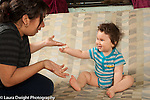 10 month old baby boy enjoying hand gesture game with aunt