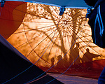 The rising sun backlights trees and passersby, throwing shadows through the material of a balloon on the ground as it is inflated.  Balloon Festival, Long Branch Farm, Winchester, Virginia, USA.  © RickCollier.com.