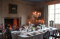 The panelled dining room is laid for dinner, with a fire glowing in the grate and candles casting a soft and atmospheric light