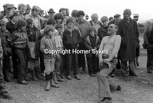 Appleby in Westmorland. 1981  <br /> Johnny Eagle the famous gypsy strongman, showman and escapologist watched by a crowd of travellers, tears a book in half.