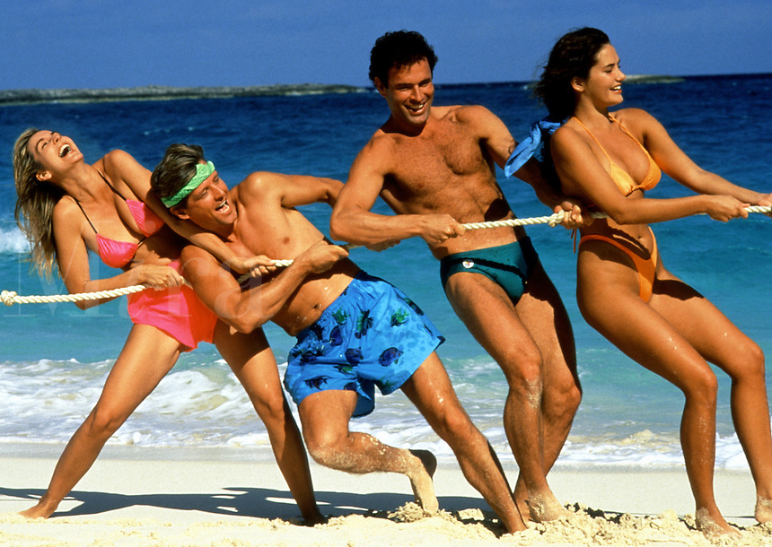 Young couples in swimsuits play tug of war on the beach.