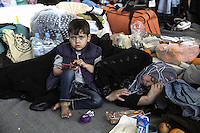 Pictured: A young boy sits right next to his mother resting on the ground at the passenger terminal Thursday 03 March 2016<br />