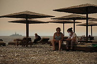 Pictured: Local residents take shelter at a beach near the village of Pefki in northern Evia siland, Greece. Sunday 08 August 2021<br /> Re: Forest fire in northern Evia, Greece.