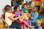 Education preschool 4 year olds group of girls in pretend play area actiing out scene with stuffed animals laughing and talking