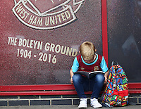 A young West Ham reads the match day programme    before  the Barclays Premier League match between West Ham United and Swansea City  played at Boleyn Ground , London on 7th May 2016
