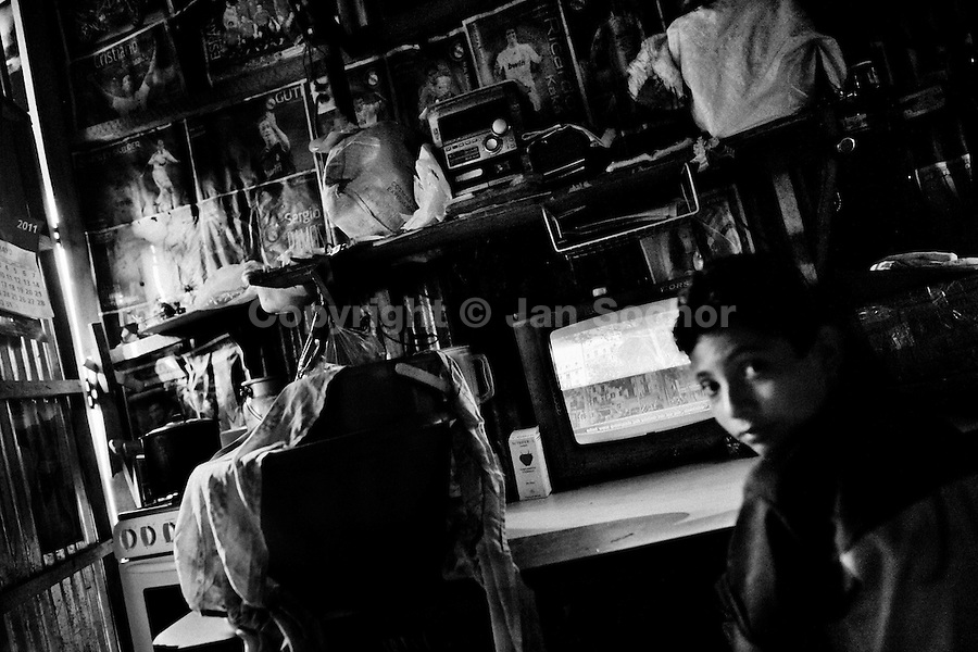 A young boy watches TV in a dark poor house located in the Mara Salvatrucha gang neighborhood in San Salvador, El Salvador, 19 May 2011. During the last two decades, Central America has become the deadliest region in the world that is not at war. According to the UN statistics, more people per capita were killed in El Salvador than in Iraq, in recent years. Due to the criminal activities of Mara Salvatrucha (MS-13) and 18th Street Gang (M-18), the two major street gangs in El Salvador, the country has fallen into the spiral of fear, violence and death. Thousands of Mara gang members, both on the streets or in the overcrowded prisons, organize and run extortions, distribution of drugs and kidnappings. Tattooed armed young men, mainly from the poorest neighborhoods, fight unmerciful turf battles with their coevals from the rival gang, balancing between life and death every day. Twenty years after the devastating civil war, a social war has paralyzed the nation of El Salvador.
