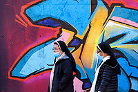 Nouns wearing face masks passing by during the initiative 'Writers united' to support the street artist Geco, recently identified, searched and reported to the police for damage to the city of Rome. To support the writer this morning many artists, gathered in Tor Bella Monaca, a suburban neighborhood of Rome and painted a long wall along the main street.<br /> Rome (Italy), December 20th 2020<br /> Photo Samantha Zucchi Insidefoto