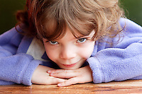 Five year old girl resting chin on table