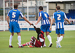 Hartlepool United 0 Middlesbrough 0, 20/07/2013. Victoria Ground, Pre-Season Friendly. Hartlepool United defenders Sam Collins, Simon Walton and Neil Austin offering a helping hand to visiting forward Marvin Emnes during the first-half at the Victoria Ground, Hartlepool, during a pre-season friendly between the home team and Middlesbrough. Hartlepool were relegated to League Two at the end of the 2012-13 season whilst their Teesside neighbours remained two divisions above them in the Championship. The game ended in a no-score draw watched by a crowd of 2307. Photo by Colin McPherson.