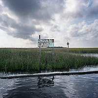 The predominantly Native American community of Pointe Aux Chene, Louisiana has been retreating inland since the 1940s due to massive coastal erosion that brought salt water into areas where fresh water was once available. Signs like this mark areas that were once settled and still contain sacred burial mounds on land ridges now accessible only by boat. After the 2010 oil spill, local tribes were concerned that these sacred areas would be contaminated with oil, and members of the tribe where hired by BP to lay absorbent boom to help protect Indian land which is granted extra protection under government legislation.