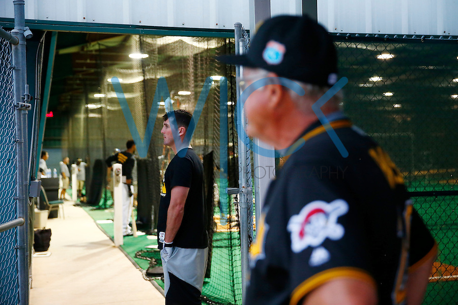 Jake Goebbert #23 of the Pittsburgh Pirates and Steve Blass look out from the batting cages as a morning storm rolls through during spring training at Pirate City in Bradenton, Florida on February 24, 2016. (Photo by Jared Wickerham / DKPS)