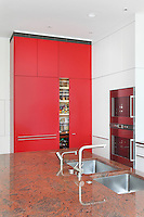 A door in the red kitchen unit of this Bulthaup kitchen slides back to access shelving