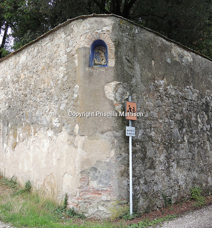 Val d'Arno, Italy - October 2, 2012:  A ceramic Madonna and Child is set into the corner of a high stone wall.