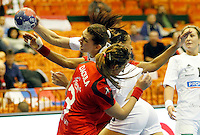 Hungaryís Klara Szekeres (C) vies with  Tunisia's Nesrine Daoula (FRONT) during their Women's Handball World Championship 2013 match Tunisia vs Hungary on December 9, 2013 in Novi Sad.   AFP PHOTO / PEDJA MILOSAVLJEVIC