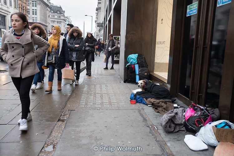 Dog and possessions of a rough sleeper in a shop doorway, Oxford Street, London.