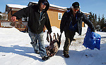 Vuntut Gwitchin members, Stanley Njootli Jr. and Stanley Njootli Sr., haul a frozen caribou in front of their home in Old Crow, Yukon Territory, Canada.