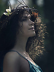 Artistic closeup portrait of a young beautiful woman face with a subtle smile and a serene, daydreaming expression, wearing a wreath made of wild flowers and tree branches in her long curly brown hair with outdoor nature scenery in the background