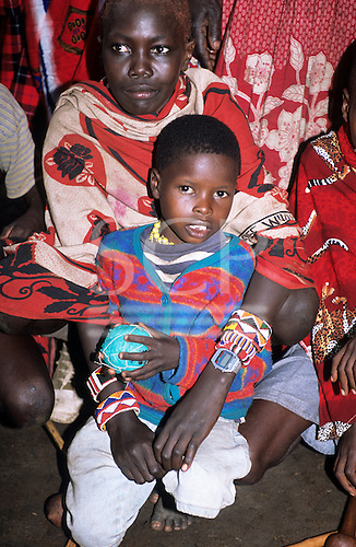 Lolgorian, Kenya. Portrait of a young boy in western clothes holding ball of plastic bags with his Maasai family wearing shukkas.