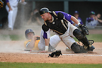 Andrew Moritz (4) of the UNC Greensboro Spartans is safe at home as the ball slips past catcher Cameron Whitehead (16) of the Furman Paladins in the title game of the Southern Conference Championship series on Sunday, May 28, 2017, at Fluor Field at the West End in Greenville, South Carolina. UNCG won, 13-1. (Tom Priddy/Four Seam Images)