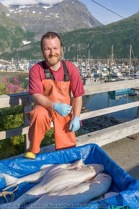 Local halibut fisherman John Guffey poses with a catch in Whittier, Alaska.