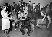 1969 File - <br /> <br /> Doing A Thank You Limbo last night; Father Michael O'Connor weaves his way beneath a stick held by Mrs. Pamela Cruickshank to demontrate Trinidad limbo dance to guests at a party in his honor at Maple Community Centre. Mrs. Cruickshank founded a group that sends supplies to children at his Trinidad school.<br /> <br /> Photo : Boris Spremo - Toronto Star archives - AQP