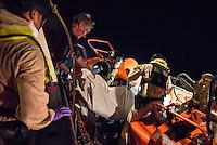 """Die Sea Watch-2 Crew war am Freitag den 21. Oktober 2016 in den fruehen Morgenstunden waehrend ihrer 13. SAR-Mission vor der libyschen Kueste zu einer Position ausserhalb der 12 Meilenzone gerufen worden. Es war ein Fluechtlingsschlauchboot gesichtet worden. Als die Sea Watch-2 dort eintraf sah sie ca. 150 Menschen zusammengepfercht in einem ueberfuellten Schlauchboot sitzen. Eine Versorgung der Menschen auf dem Fluechtlingsschlauchboot mit Rettungswesten durch die Rettungs Boote der Sea Watch-2 wurde von der libyschen Kuestenwache unterbunden. Ein Soldat der Kuestenwache enterte das Schlauchboot vom Bug und machte sich dann an dem Aussenbordmotor zu schaffen. Auf dem Weg dahin schlug und trat er die Gefluechteten ein. Nach einigen Minuten entfernte sich das Boot der Kuestenwache. Dann verlor der Bug des Schlauchbootes seine Luft und es brach Panik bei den Gefluechteten aus. Sie sprangen in das Wasser und versuchten zum Schiff Sea Watch-2 zu gelangen. Die Crew warf ihnen Schwimmwesten und Rettungsringe zu, die Besatzungen der Rettungsboote der Sea Watch-2 zogen Menschen aus dem Meer, dennoch sind bis zu 30 Menschen ertrunken. Vier Ertrunkene konnten von der Sea Watch geborgen werden.<br /> Im Bild: Polizisten des norwegischen Frontex-Kommandos uebernehmen vier der am Morgen ertrunkenen Gefluechteten.<br /> 2 vl. Der """"Head of Mission"""" der Sea Watch-2.<br /> 21.10.2016, Mediterranean Sea<br /> Copyright: Christian-Ditsch.de<br /> [Inhaltsveraendernde Manipulation des Fotos nur nach ausdruecklicher Genehmigung des Fotografen. Vereinbarungen ueber Abtretung von Persoenlichkeitsrechten/Model Release der abgebildeten Person/Personen liegen nicht vor. NO MODEL RELEASE! Nur fuer Redaktionelle Zwecke. Don't publish without copyright Christian-Ditsch.de, Veroeffentlichung nur mit Fotografennennung, sowie gegen Honorar, MwSt. und Beleg. Konto: I N G - D i B a, IBAN DE58500105175400192269, BIC INGDDEFFXXX, Kontakt: post@christian-ditsch.de<br /> Bei der Bearbeitung der Dateiinf"""
