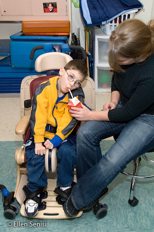 MR / Albany, NY.Langan School at Center for Disability Services .Ungraded private school which serves individuals with multiple disabilities.Teaching assistant feeds child carton of milk through a straw.  Child is in Rifton chair during snack time. Boy: 9, cerebral palsy, limited verbal output with expressive and receptive language delays.MR: Ken8; Rub1.© Ellen B. Senisi