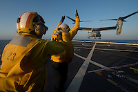130423-N-DR144-048 Pacific Ocean (April 23, 2013)-  Aviation Boatswain's Mate (Handling) 2nd Class Diego Paredes, left, assigned to Amphibious Transport Dock Ship USS Anchorage (LPD 23), trains Aviation Boatswain's Mate (Handling) Airman Katie Glendy, right, assigned to Amphibious Transport Dock Ship USS San Diego (LPD 22), as she directs an MV-22 Osprey assigned to Marine Medium Tiltrotor Squadron (VMM) 163 on Anchorage's flight deck. Air Department Sailors from San Diego are aboard Anchorage earning qualifications and maintaining proficiency while the ship is underway. Anchorage is currently en route to its namesake city of Anchorage, Alaska for its commissioning ceremony May 4. (U.S. Navy photo by Mass Communication Specialist 1st Class James R. Evans / RELEASED)