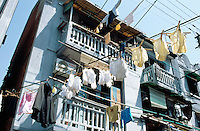 """China. Shanghai. Downtown. City center. Laundry-lined in the old """"French Concession"""" area. Early morning,  some underwears, many white gloves and a shirt just washed are now drying outside the balconies of an old traditionnal house. © 2002 Didier Ruef"""